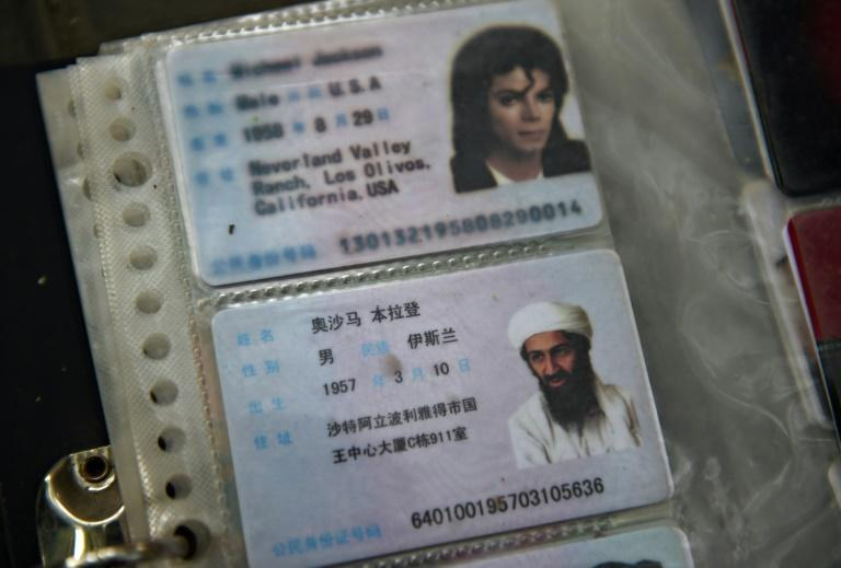 Imitation Chinese identification cards featuring Osama bin Laden and Michael Jackson for sale on a sidewalk in Beijing in 2015