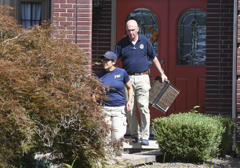 FBI investigators leave the home of UAW President Gary Jones during a search on Wednesday, August 28, 2019 in Canton, Michigan. (Max Ortiz/Detroit News via AP)