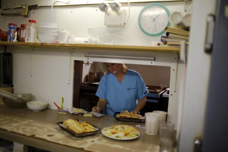 A waitress waits for plates in the kitchen of a restaurant in Bayou La Batre,
