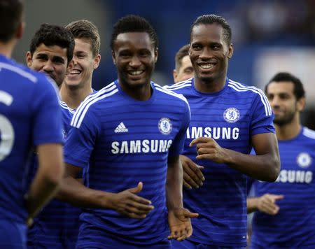 Chelsea's Drogba runs with his teammates as they warm up before their friendly soccer match against Real Sociedad at Stamford Bridge in London