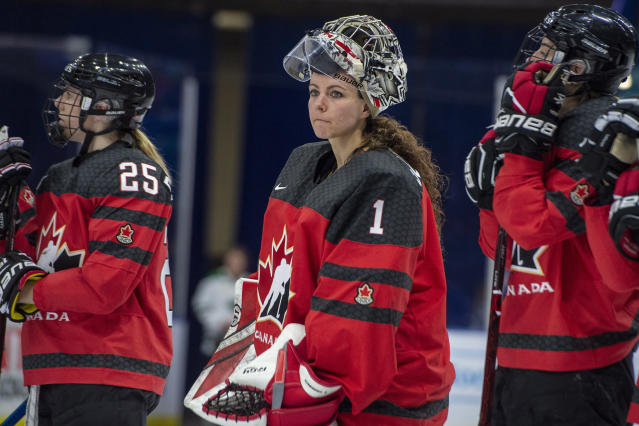 FILE - In this Nov. 10, 2018, file photo, Canada goaltender Shannon Szabados watch as U.S. players celebrate a win during the Four Nations Cup hockey gold-medal game in Saskatoon, Saskatchewan. More than 200 of the top female hockey players in the world have decided they will not play professionally in North America next season, hoping their stand leads to a single economically sustainable league. The announcement Thursday, May 2, 2019, comes after the Canadian Women's Hockey League abruptly shut down as of Wednesday, leaving the five-team, U.S.-based National Women's Hockey League as the only pro league in North America. The group of players, led by American stars Hilary Knight and Kendall Coyne Schofield and Canadian goaltender Shannon Szabados, hopes their move eventually pushes the NHL to start its own women's hockey league as the NBA did with the WNBA. (Liam Richards/The Canadian Press via AP)