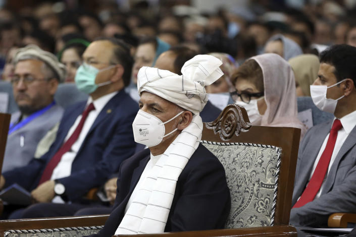 Afghan President Ashraf Ghani, center, wearing a protective face mask to help curb the spread of the coronavirus, attends an Afghan Loya Jirga meeting in Kabul, Afghanistan, Friday, Aug. 7, 2020. The traditional council opened Friday in the Afghan capital to decide the release of a final 400 Taliban - the last hurdle to the start of negotiations between Kabul's political leadership and the Taliban in keeping with a peace deal the United States signed with the insurgent movement in February. (AP Photo/Rahmat Gul)