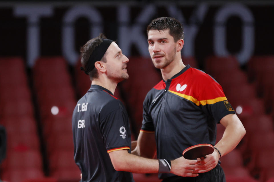 TOKYO, JAPAN - AUGUST 04: Timo Boll (L) and Dimitrij Ovtcharov (R) of Team Germany shake hands during their Men's Team Semifinals table tennis match on day twelve of the Tokyo 2020 Olympic Games at Tokyo Metropolitan Gymnasium on August 04, 2021 in Tokyo, Japan. (Photo by Steph Chambers/Getty Images)