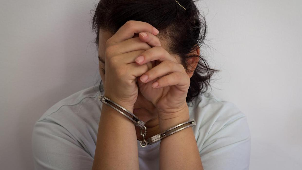 Desperate criminal woman sitting on the floor in handcuffs (Getty Images)