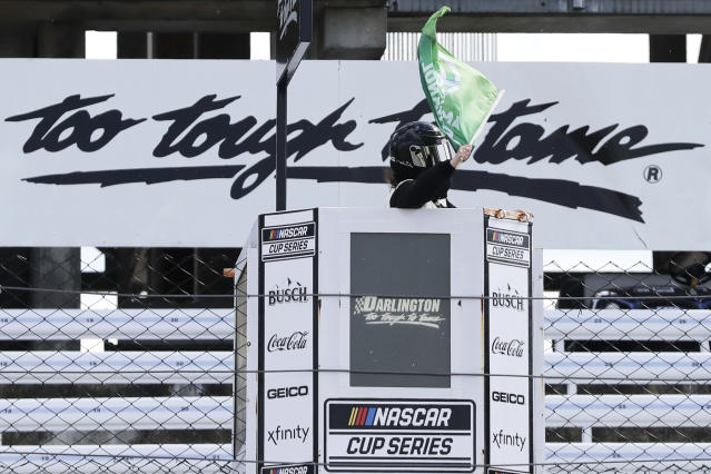 The green flag is waved to start the NASCAR Cup Series auto race Sunday, May 17, 2020, in Darlington, S.C. NASCAR, which has been idle for 10 weeks because of the coronavirus pandemic, returned to action with the Real Heroes 400 race at Darlington Raceway. (AP Photo/Brynn Anderson)