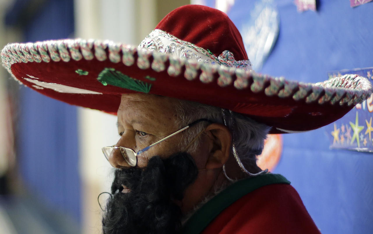 In this Friday, Dec. 20, 2013, photo, Pancho Claus, Rudy Martinez visits with students at Knowlton Elementary School, in San Antonio. Pancho Claus, a Tex-Mex Santa borne from the Chicano civil rights movement in the late 1970s and early 1980s, is now an adored Christmas fixture in many Texas cities. (AP Photo/Eric Gay)