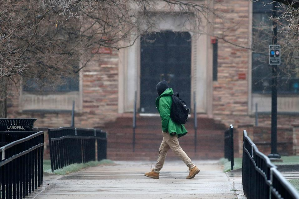 A lone pedestrian moves through the closed campus of the University of Colorado as a statewide stay-at-home order remains in effect in an effort to reduce the spread of the new coronavirus Thursday, April 2, 2020, in Boulder, Colo. The new coronavirus causes mild or moderate symptoms for most people, but for some, especially older adults and people with existing health problems, it can cause more severe illness or death. (AP Photo/David Zalubowski)