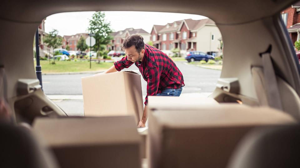 Caucasian man loading moving boxes in to his car.