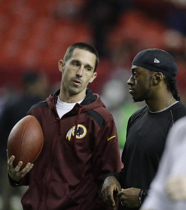 Washington Redskins quarterback Robert Griffin III, right speaks with Washington Redskins offensive coordinator Kyle Shanahan before the first half of an NFL football game against the Atlanta Falcons, Sunday, Dec. 15, 2013, in Atlanta. (AP Photo/John Bazemore)