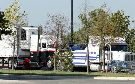 FILE PHOTO: Police prepare to tow and 18-wheeler trailer parked behind a Walmart store after eight people believed to be illegal immigrants being smuggled into the United States were found dead inside it in San Antonio, Texas, U.S. July 23, 2017.   REUTERS/Ray Whitehouse/File Photo