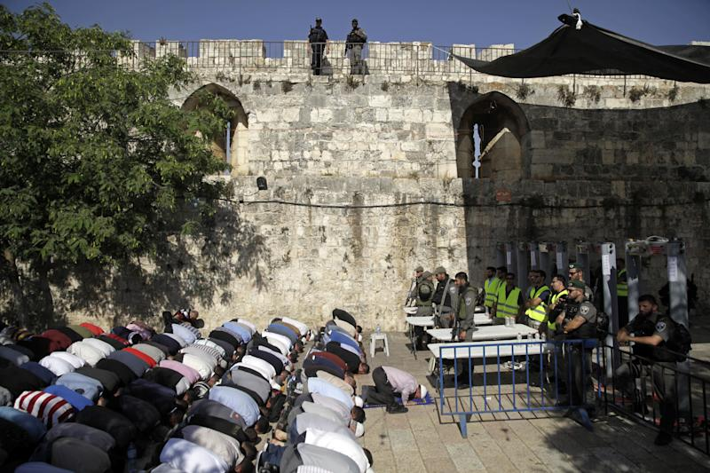 Israeli border police officers stand guard as Muslim men pray outside the Al Aqsa Mosque compound, in Jerusalem, Sunday, July 16, 2017. Adnan Husseini, the Palestinian Minister of Jerusalem, said Sunday that arrangements at the Muslim-administered holy site need to return to how they were before a deadly attack last week, in which three Arab Israelis shot dead two police officers before being killed. (AP Photo/Mahmoud Illean)