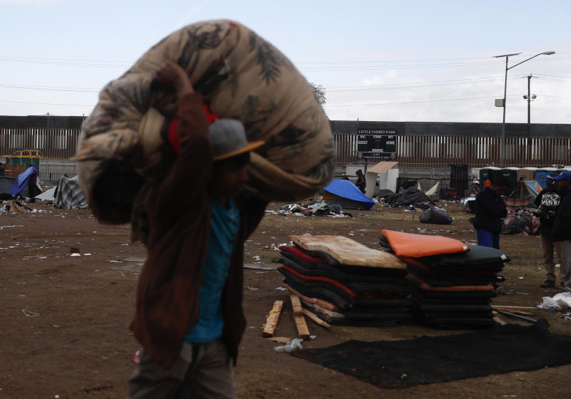 A migrant helps bundle and clear trash as most Central Americans leave a sports complex shelter that authorities were trying to close in Tijuana Mexico Saturday Dec. 1 2018. By Saturday afternoon most of the thousands of migrants who had been camped