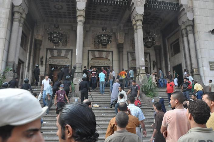A group of Egyptians gather at the al-Fatah mosque, after hundreds of Muslim Brotherhood supporters barricaded themselves inside the mosque overnight, following a day of fierce street battles that left scores of people dead, near Ramses Square in downtown Cairo, Egypt, Saturday, Aug. 17, 2013. Authorities say police in Cairo are negotiating with people barricaded in a mosque and promising them safe passage if they leave. Muslim Brotherhood supporters of Egypt's ousted Islamist president are vowing to defy a state of emergency with new protests today, adding to the tension. (AP Photo/Hussein Tallal)