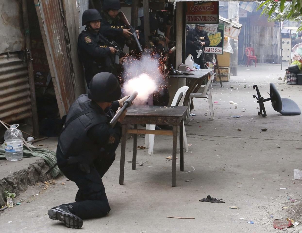 A policeman fires teargas during clashes with squatters at a squatter district in Quezon city