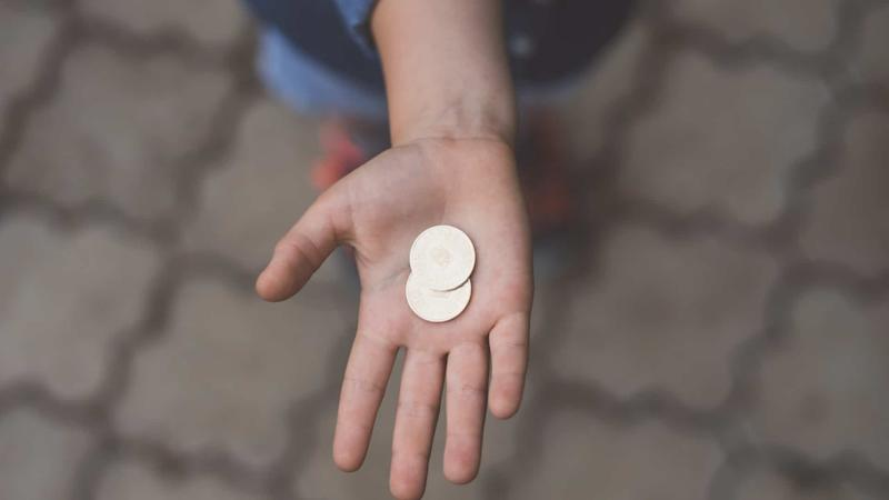 hand outstretched with two coins in palm
