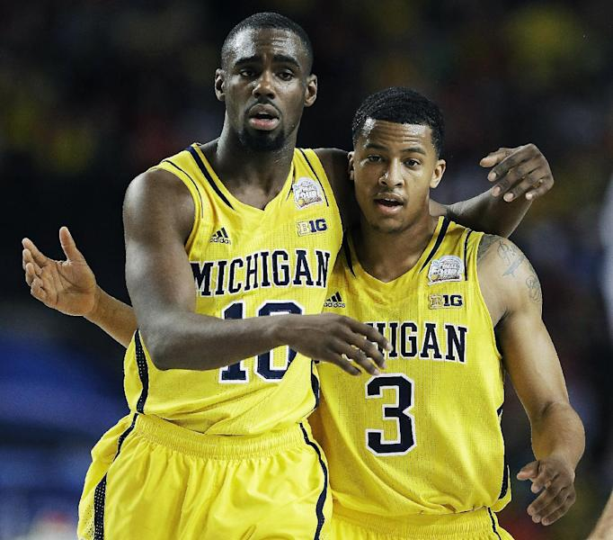 Michigan's Trey Burke, right, and teammate Tim Hardaway Jr. walk down the court during the second half of their NCAA Final Four tournament college basketball semifinal game against Syracuse, Saturday, April 6, 2013, in Atlanta. Michigan won 61-56. (AP Photo/Charlie Neibergall)