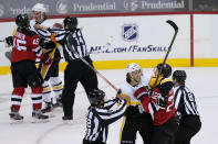 Pittsburgh Penguins center Mark Jankowski (14) and New Jersey Devils defenseman Ryan Murray (22) scuffle during a stoppage in play during the second period of an NHL hockey game, as an officials moves to separate players at upper left Thursday, March 18, 2021, in Newark, N.J. (AP Photo/John Minchillo)