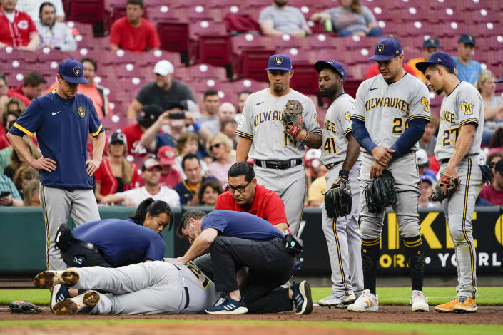 Training staff attend to Milwaukee Brewers' Travis Shaw during the second inning of the team's baseball game against the Cincinnati Reds in Cincinnati on Wednesday, June 9, 2021. (AP Photo/Jeff Dean)