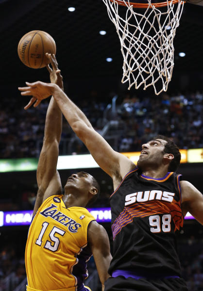 Los Angeles Lakers' Metta World Peace (15) gets fouled as he goes up for a shot against Phoenix Suns' Hamed Haddadi (98), of Iran, in the first half of an NBA basketball game, Monday, March 18, 2013, in Phoenix. (AP Photo/Ross D. Franklin)