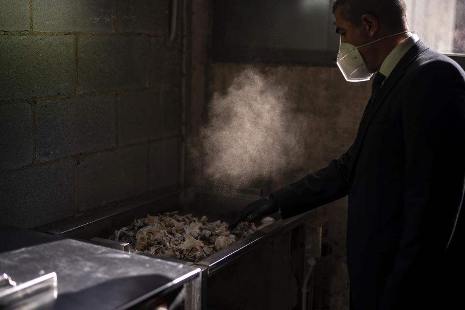 A mortuary worker collects the ashes of a COVID-19 victim from an oven after the remains where cremated at Mémora mortuary in Girona, Spain, Thursday, Nov. 19, 2020. (AP Photo/Emilio Morenatti)