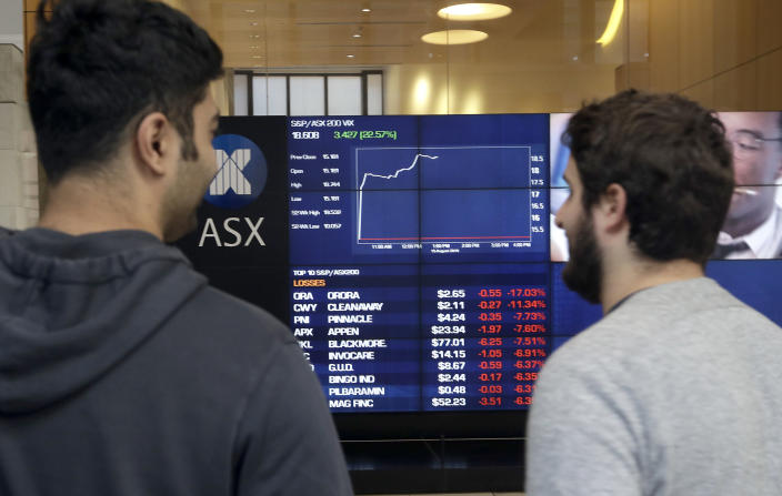 Men watch the public display boards at the Australian Stock Exchange in Sydney, Thursday, Aug. 15, 2019. Asian stock markets followed Wall Street lower on Thursday after the Dow Jones Industrial Average plunged on mounting fears of a possible recession. (AP Photo/Rick Rycroft)