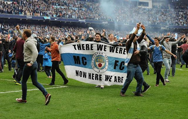 Manchester City's fans invade the pitch after the final whistle, as Manchester City are crowned Premier League Champions after the English Premier league soccer match between Manchester City and West Ham United at the Etihad Stadium, Manchester, England, Sunday, May 11, 2014. (AP Photo/Rui Vieira)