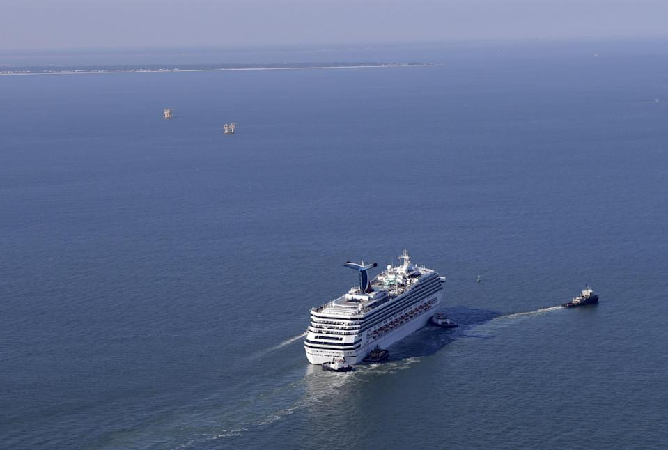A disabled Carnival Lines cruise ship is towed to harbor off Mobile Bay, Ala., Thursday, Feb. 14, 2013. The ship with more than 4,200 passengers and crew members has been idled for nearly a week in the Gulf of Mexico following an engine room fire. (AP Photo/Gerald Herbert)
