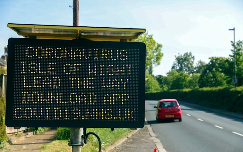 A sign telling people in the Isle of Wight to download the NHS coronavirus contact tracing app -Isle of Wight contact tracing trial undermined by people on UK mainland downloading the app - PA
