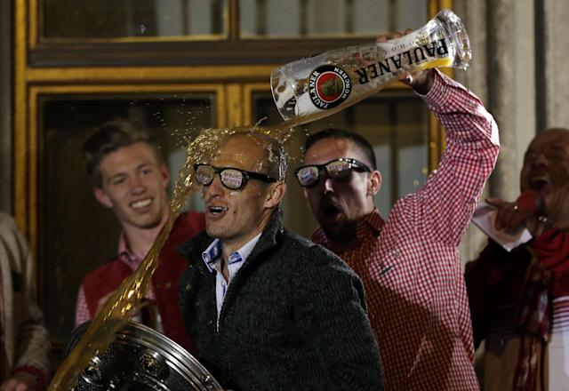 Bayern's Franck Ribery of France showers teammate Bayern's Arjen Robben of the Netherlands with beer on the town hall balcony after winning the German Soccer Championship after the season's last home game between FC Bayern Munich and VfB Stuttgart, in Munich, southern Germany, Saturday, May 10, 2014. (AP Photo/Matthias Schrader)