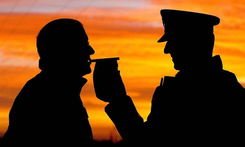 A police officer gives a motorist a breath test