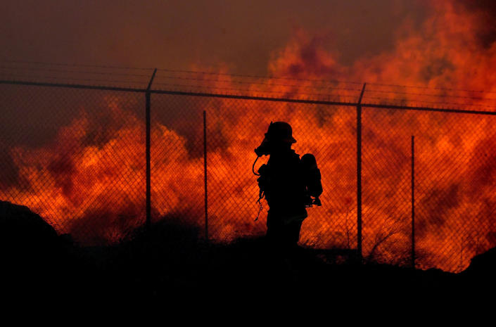 A firefighter walks past a wall of fire as multiple agencies battle a mulch and pallet fire burning out of control, fanned by Santa Ana winds in and around a recycling yard near Wilson Street and Fleetwood Drive in Riverside, Calif., Thursday, Dec. 3, 2020. Firefighters from both Riverside and San Bernardino County, along with assistance from Colton, Rialto and Riverside City Fire fought the blaze. (Will Lester/The Orange County Register via AP)