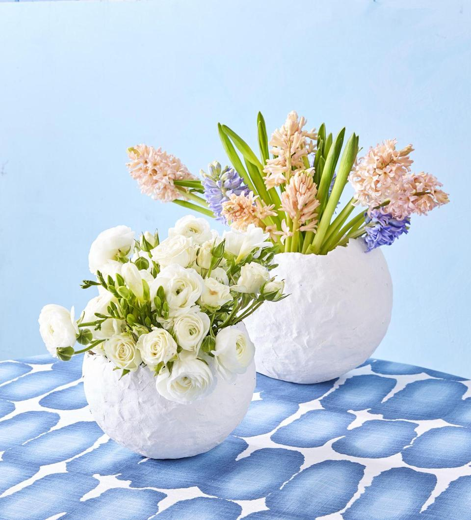 """<p>These papier-mâché vases are ideal for serving candy or holding a beautiful bouquet.</p><p><strong>To make:</strong> Blow up a large and a medium balloon. Cover each with white papier-mâché craft paper, leaving bottom quarter to third uncovered and edges rough. Let dry. Pop balloons, and remove. Set a vase inside each, and fill with water and flowers.</p><p><a class=""""link rapid-noclick-resp"""" href=""""https://www.amazon.com/White-Kraft-Arts-Crafts-Paper/dp/B086CDT13X/ref=sr_1_11?tag=syn-yahoo-20&ascsubtag=%5Bartid%7C10050.g.1111%5Bsrc%7Cyahoo-us"""" rel=""""nofollow noopener"""" target=""""_blank"""" data-ylk=""""slk:SHOP PAPER"""">SHOP PAPER</a></p>"""