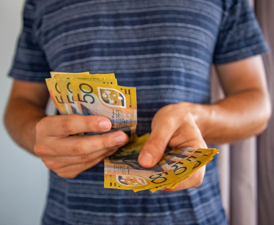 Man handling fifty dollar notes finance.