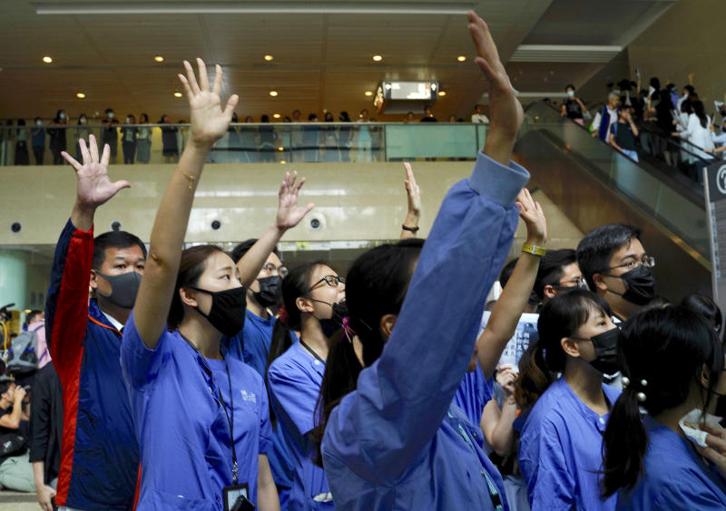 Medical workers display opened palm with five fingers, signifying the five demands of protesters and chanted slogans as they stood in the foyer of the hospital before moving to different floors of the building at the Prince of Wales Hospital in Hong Kong, Monday, Sept. 16, 2019. The anti-government protests have taken place since June and increasingly have been marked by violence and clashes with police. (AP Photo/Vincent Yu)