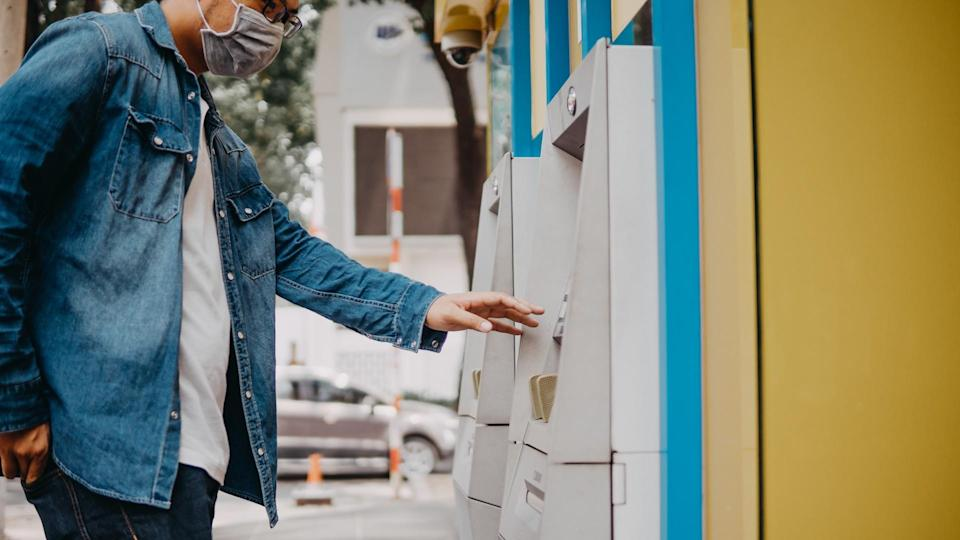Young asian man wearing medical mask withdraw money from bank cash machine with debit card - Senior male doing payment with credit card in ATM - Concept of business, banking account and lifestyle people.