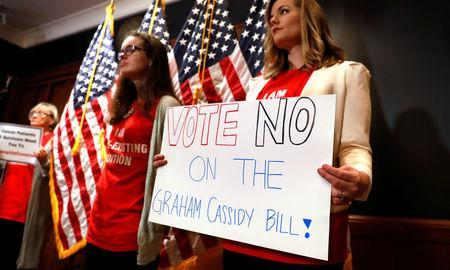 Women hold signs during a press conference held by U.S. Sen. Bob Casey, D-Pa., to speak out against the latest Republican effort to repeal Obamacare on Capitol Hill in Washington, U.S., September 25, 2017. REUTERS/Kevin Lamarque