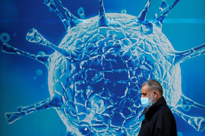 A man wearing a protective face mask walks past an illustration of a virus outside a regional science centre, as the city and surrounding areas face local restrictions in an effort to avoid a local lockdown being forced upon the region, amid the coronavirus disease (COVID-19) outbreak, in Oldham, Britain August 3, 2020. REUTERS/Phil Noble