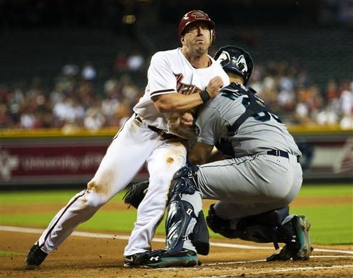 Arizona Diamondbacks' Willie Bloomquist knocks the ball away from Seattle Mariners catcher Jesus Montero while scoring during the first inning of an interleague baseball game, Monday, June 18, 2012, in Phoenix. (AP Photo/The Arizona Republic, Michael Chow) MARICOPA COUNTY OUT; MAGS OUT; NO SALES