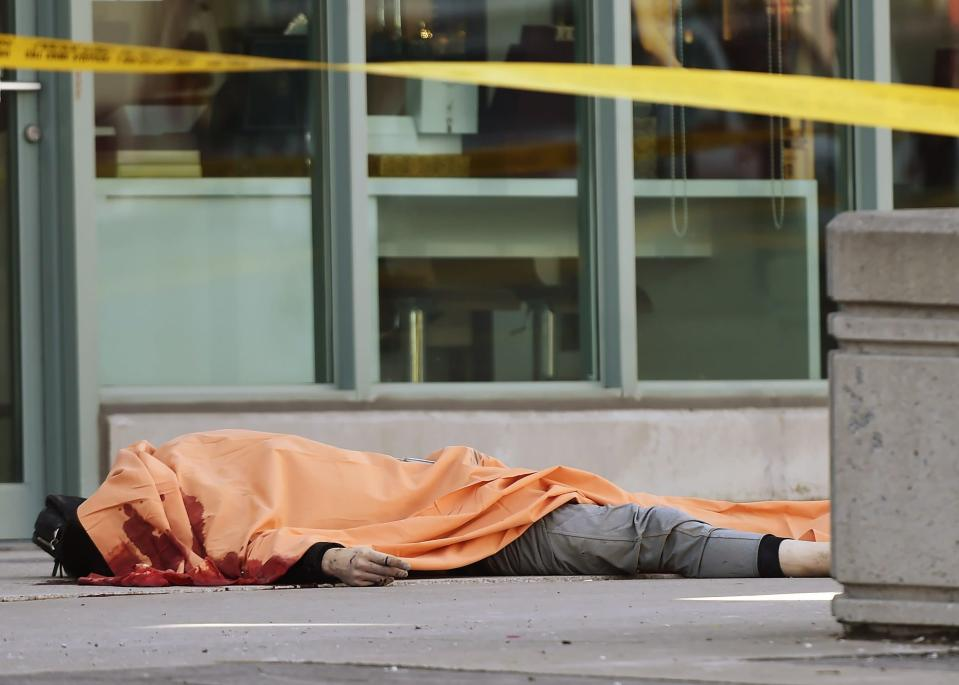 <p>A covered body is seen in Toronto after a van mounted a sidewalk crashing into a number of pedestrians on Monday, April 23, 2018. THE CANADIAN PRESS/Nathan Denette </p>