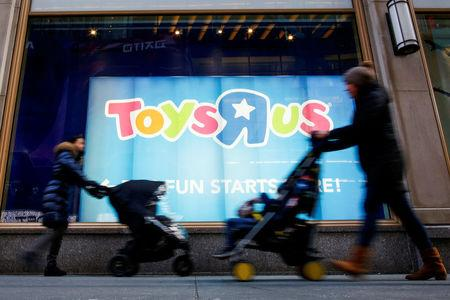 People pass by Toys R Us store at Times Square in New York