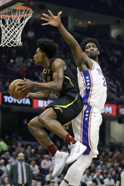 Cleveland Cavaliers' Collin Sexton, left, drives to the basket against Philadelphia 76ers' Joel Embiid in the first half of an NBA basketball game, Wednesday, Feb. 26, 2020, in Cleveland. (AP Photo/Tony Dejak)