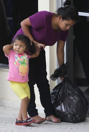 A woman holds her daughter's hand as she grabs a plastic bag with their belongings, after being deported from the U.S. at the international airport in San Pedro Sula, northern Honduras July 14, 2014. REUTERS/Jorge Cabrera