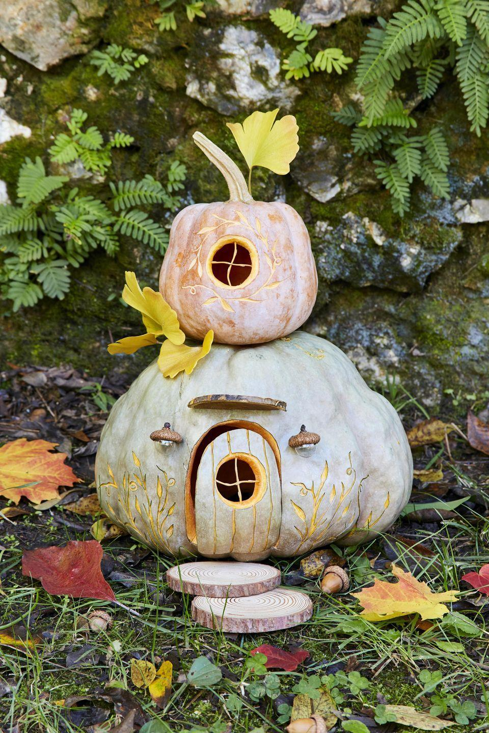 <p>Little hands will love helping create and keeping and eye out for the gnomes that are surely going to move into this sweet little gourd cottage. To display, try setting on a table on a soft bed of moss.</p><p><strong>To make:</strong> Cut a hole in the bottom of a medium blue Hubbard squash; scoop out the pulp and seeds. Cut out the door and circular door window. Etch lines in the door with a linoleum carving tool and insert toothpicks (shortened if necessary) to create window muttons. Lightly draw flower design on either side of door with a pencil and use linoleum carving tool to etch out. Insert the door into the opening and hold in place with toothpicks. Hot glue mini glass balls into acorn caps to create lights; attach to pumpkin with hot glue. Cut half to 2/3 off of a wood round; attach to pumpkin, above the door, to create an awning.</p><p>Cut a hole in the bottom of a small brown or green acorn squash; scoop out the pulp and seeds. Cut a circular window and insert toothpicks (shortened if necessary) to create window muttons. Lightly draw flower design around window with a pencil and use linoleum carving tool to etch out. Stack pumpkins and add wood round steps and gingko leaves.</p>