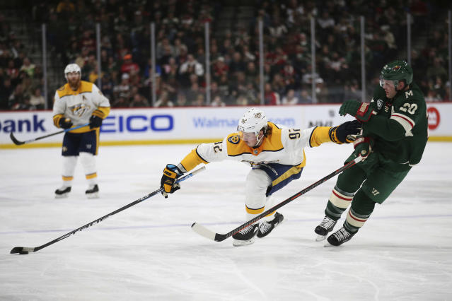 Nashville Predators' Ryan Johansen reaches for the puck in front of Minnesota Wild's Ryan Suter during the second period of an NHL hockey game, Sunday, March 3, 2019, in St. Paul, Minn. (AP Photo/Stacy Bengs)