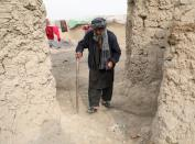 An internally displaced Afghan man walks next to his shelter on the outskirts of Kabul