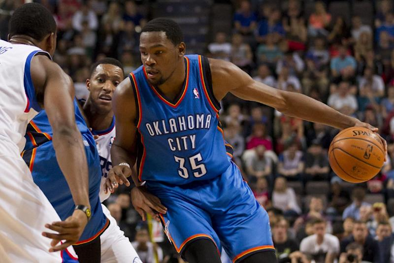 Oklahoma City Thunder's Kevin Durant, right, keeps the ball from Philadelphia 76ers' Thaddeus Young, left, as Evan Turner, centre left, looks on during their NBA preseason basketball game at the Phones4 u Arena in Manchester, England, Tuesday, Oct. 8, 2013. (AP Photo/Jon Super)