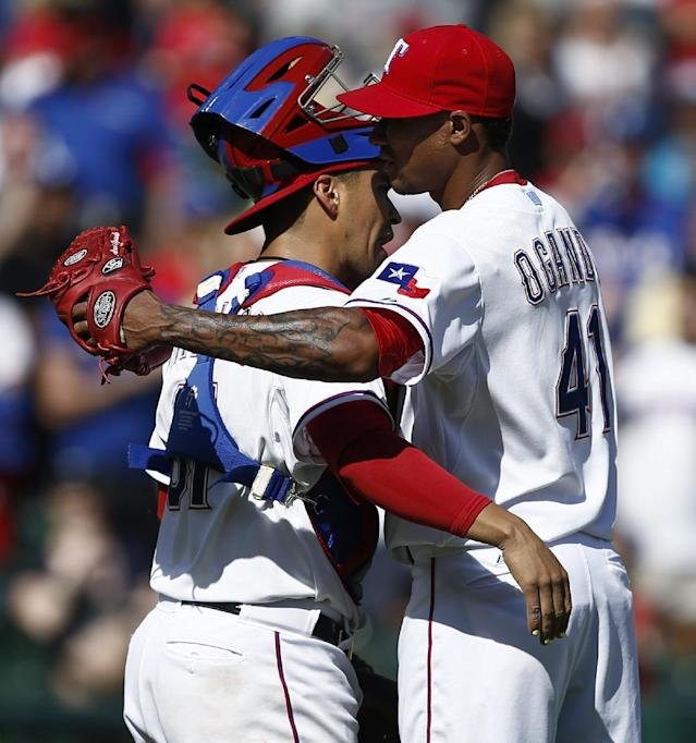 Texas Rangers starting pitcher Alexi Ogando (41) and catcher Robinson Chirinos (61) congratulate each other after the Rangers' 1-0 win against the Houston Astros in a baseball game, Sunday, April 13, 2014, in Arlington, Texas. (AP Photo/Jim Cowsert)