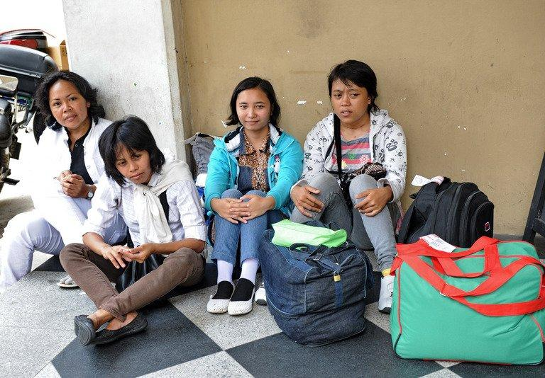 Indonesian domestic staff wait for their transportation to a maid agency in Singapore, on March 6, 2012