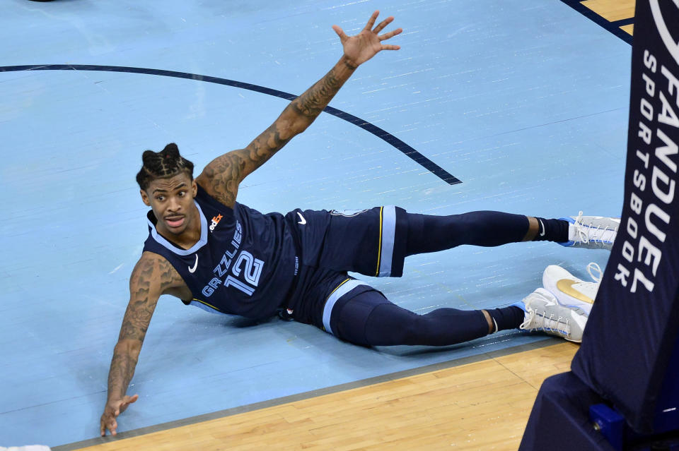 Memphis Grizzlies guard Ja Morant (12) looks to a referee after scoring in the second half of an NBA basketball game against the Milwaukee Bucks, Thursday, March 4, 2021, in Memphis, Tenn. (AP Photo/Brandon Dill)