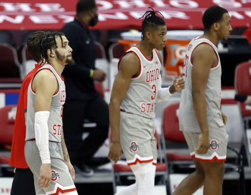 Ohio State guard Duane Washington, left, guard Eugene Brown, and forward Zed Key leave the bench following an NCAA college basketball game loss to Purdue in Columbus, Ohio, Tuesday, Jan. 19, 2021. (AP Photo/Paul Vernon)
